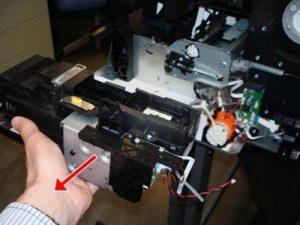 Аккуратно извлеките сервисную станцию (ёмкость для отработанных чернил) из устройства